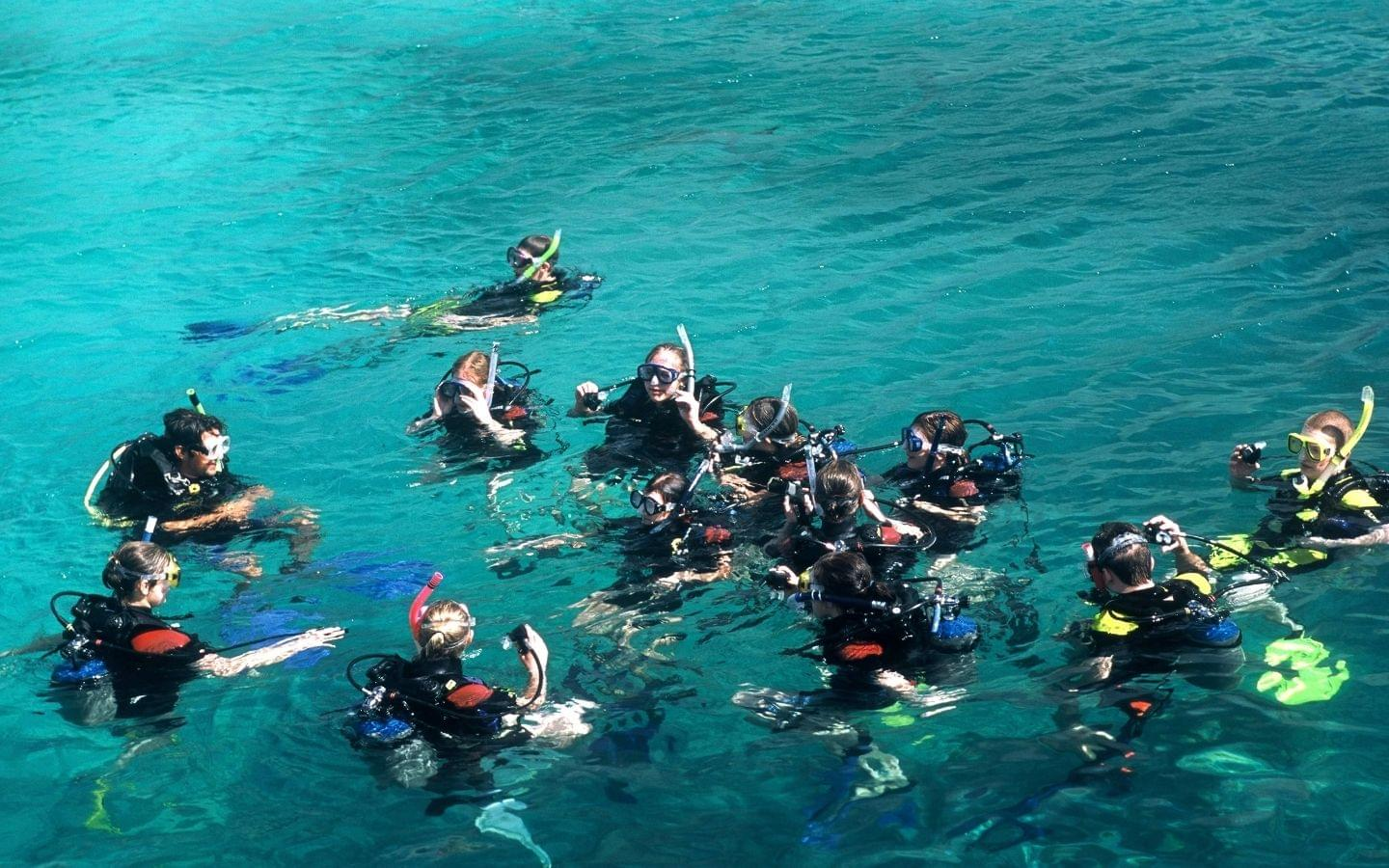 scuba diving instructor leading a group of divers in a lesson