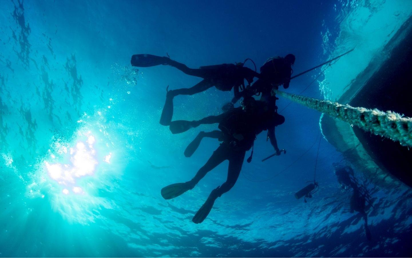 diving underwater on anchor line off boat