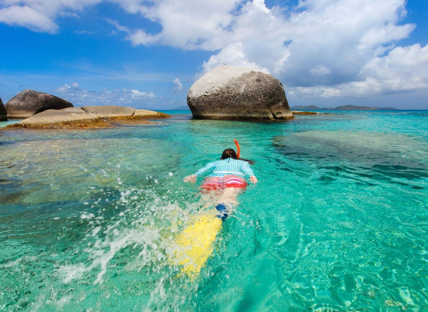 woman snorkeling around rocks